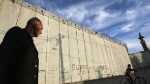Un palestinien marchant le long de la barrière de sécurité du côté du village d'Abu dis à Jérusalem-Est (Crédit : Kobi Gideon/Flash90)