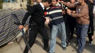 Un policier arrête un partisan des Frères musulmans le 25 janvier 2014 au Caire (Crédit AFP/Mohamed el-Shahed)