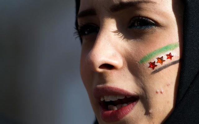 Vendredi 24 janvier 2014, devant le siège de l'Onu à Genève, une manifestante contre le régime de Bachar al-Assad, maquillée aux couleurs nationales syriennes. (Crédit : AFP/Fabrice Coffini)
