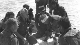Haim Bar-Lev (Centre gauche) consulte Ariel Sharon (avec le bandage) et Moshe Dayan (casquette) sur le front sud pendant la guerre du Kippour (Crédit : GPO/ Flash90)