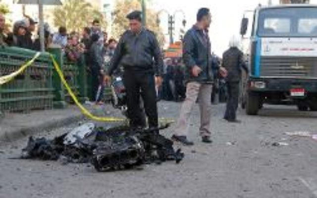 Des policiers et habitants sur les lieux d'un attentat à la voiture piégée devant le quartier général de la police, le 24 janvier 2014 au Caire. (Crédit: AFP/Khaled Kamel)