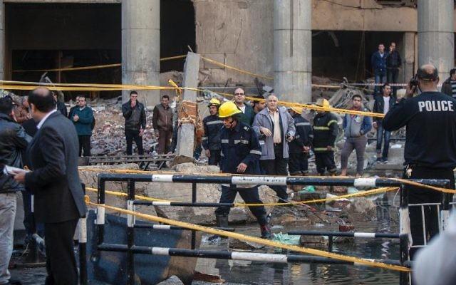 Des équipes de secours et des habitants sur les lieux d'un attentat visant le quartier général de la police, le 24 janvier 2014 au Caire (Crédit : AFP/Mahmoud Khaled)