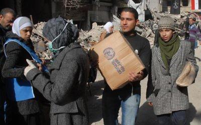Des réfugiés palestiniens du camp de Yarmouk, au sud de Damas, reçoivent de l'aide alimentaire, le 30 janvier 2014 (Crédit: Sana/AFP)