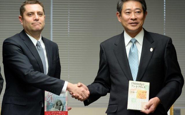 Le chef adjoint de l'ambassade d'Israël, Peleg Lewi (G) et Ryo Tanaka, le maire de l'arrondissement de Suginami à Tokyo lors d'une cérémonie pour le don de 300 exemplaires du Journal d'aNNe Frank, 27 février 2014 (Crédit : Toshifumi Kitamura/AFP)