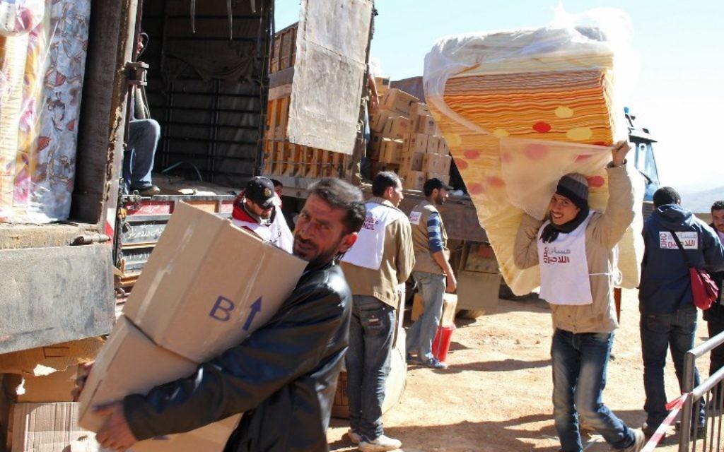 Des aides déchargent des dons de matériel dans un camp de réfugiés syriens au Liban, 18 février 2014. Illustration. (Crédit : AFP/STR)