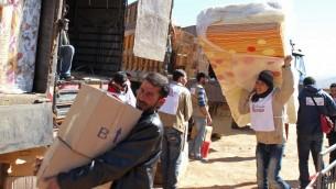 Des aides déchargent des dons de matériel dans un camp de réfugiés syriens au Liban près de la frontière, 18 février 2014 (Credit : AFP PHOTO / STR)