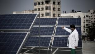 Un médecin palestinien montre les panneaux solaires installés sur les toits de l'hôpital des enfants à Gaza, 24 février 2014 (Crédit : Mahmud Hams/AFP)