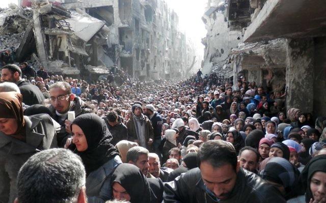La file interminable de réfugiés lors d'une distribution de nourriture organisée par l'ONU, dans les ruines du camp de réfugiés de Yarmouk, au sud de Damas (Crédit : AFP Photo/HO/UNRWA)