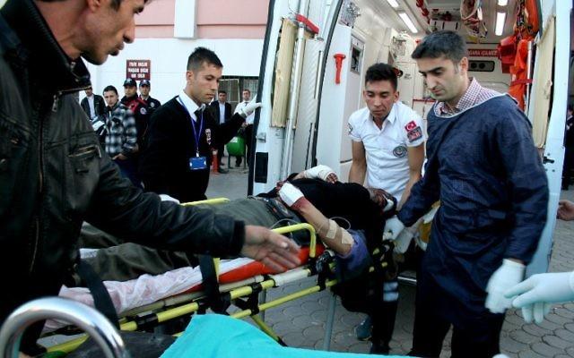 Des Turcs aident des blessés syriens après une explosion près de la frontière syro-turque, le 20 février 2014 (Crédit : Mehmet Engin/AFP)