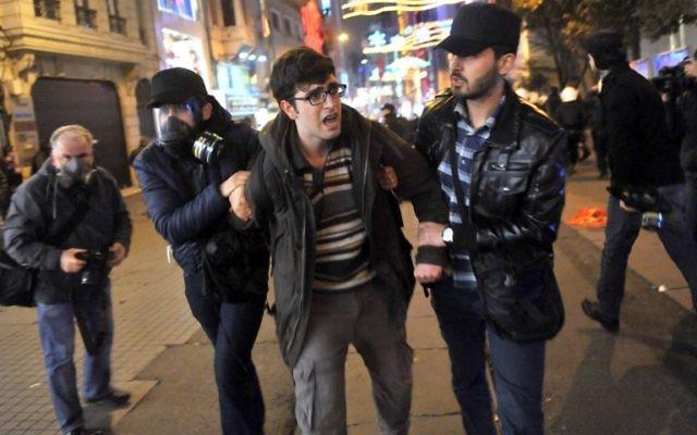 Des officiers de police en civil arrête un jeune manifestant lors des émeutes contre le nouveau projet de loi, 22 février 2014 (Crédit : AFP/Ozan Kose)