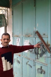 Zidan Sharabati montre la barre de fer forgée sur les portes de son magasin dans la rue Shuhada (Crédit : Elhanan Miller/Times of Israel)