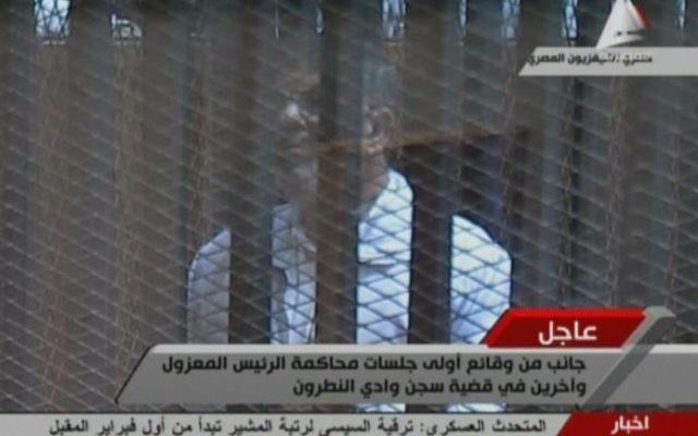 Image diffusée par la télévision égyptienne du président destitué Mohamed Morsi, portant l'uniforme blanc des détenus, au Caire le 28 janvier 2014.  (Crédit : TV égyptienne/AFP/Archives)