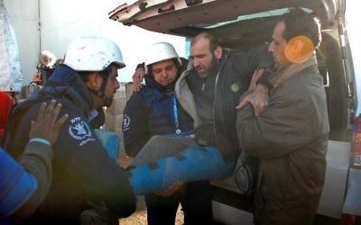 Un Syrien blessé évacué des quartiers assiégés de Homs, le 12 février 2014 lors d'une opération humanitaire (Crédit : AFP)
