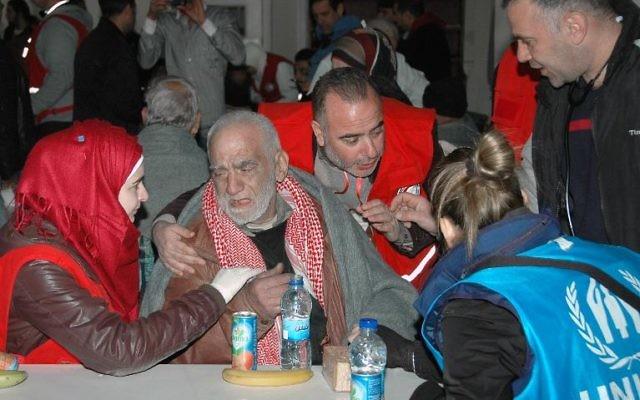 Des civils reçoivent de l'aide alimentaire à Homs le 7 février (Crédit : Sana/AFP)
