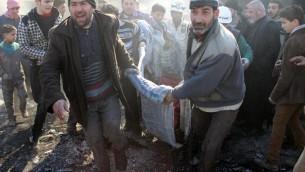 Des hommes transportent une victime, après un bombardement sur la ville d'Alep, le 1er février 2014  (Crédit : AMC/AFP Zein Al-Rifai)