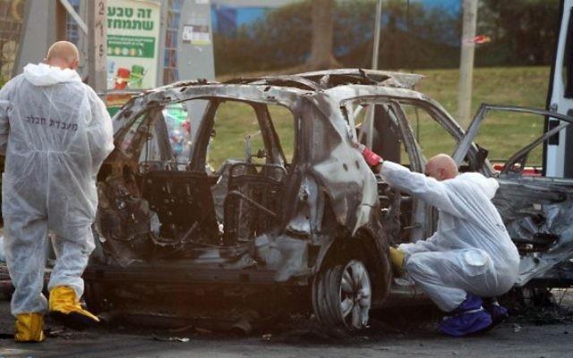 Des policiers enquêtent sur le véhicule, alors qu'une bombe a explosé dans la ville de Petach Tikva (Crédit :    Gideon Markowicz/Flash90)
