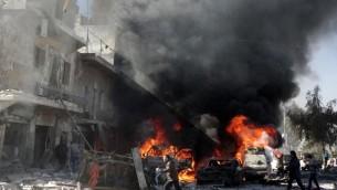 Des voitures en flammes après un bombardement sur la ville d'Alep, le 1er février 2014  (Crédit : AFP/Mohammed Al-Khatieb)