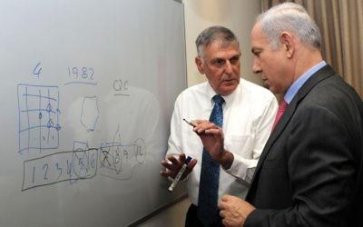 Le professeur Shechtman explique une théorie au Premier ministre Benjamin Netanyahu. (Crédit : Amos Ben Gershom/GPO/Flash90)
