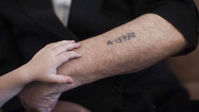 Un petit garçon met sa main sur le bras de son grand-père, près de son tatouage de prisonnier de camp de concentration, à Jérusalem, le 24 mai 2013. (Crédit : Yonatan Sindel/Flash90)