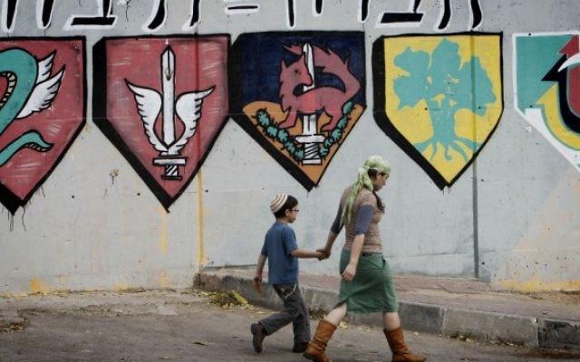 Des habitants juifs des implantations passent à côté d'une base de l'armée israélienne à Hébron. (Crédit : Miriam Alster/Flash90)