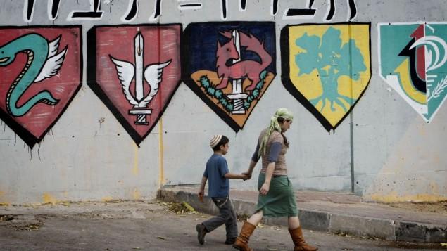 Des colons juifs passant à côté d'une base de l'armée israélienne à Hébron. (Crédit : Miriam Alster/Flash90)