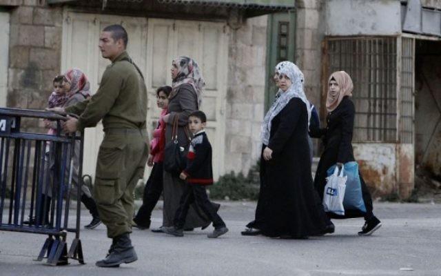 Des femmes arabes passent à côté d'un soldat israélien en patrouille dans la ville divisée de Hébron en Cisjordanie. (Crédit : Miriam Alster/Flash90)