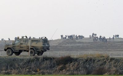 Des Palestiniens manifestent près de la barrière à la frontière entre Israël et la bande de Gaza alors qu'une jeep de l'armée israélienne patrouille à la frontière, 3 janvier 2014. (Crédit : David Buimovitch/Flash90)