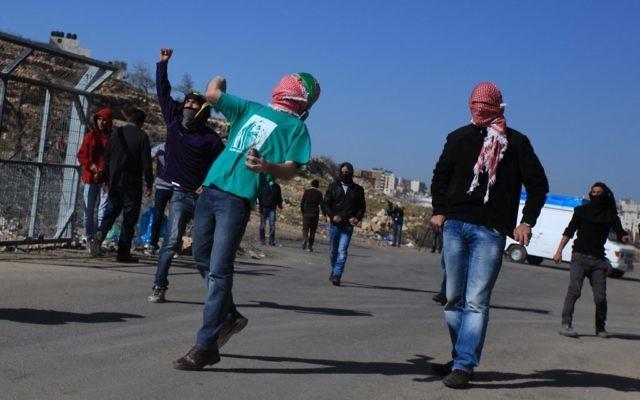 Des étudiants de l'université de Bir Zeit lancent des pierres vers l'armée israélienne près de Ramallah, 30 janvier 2014 (Crédit : Issam Rlmawi/Flash90)