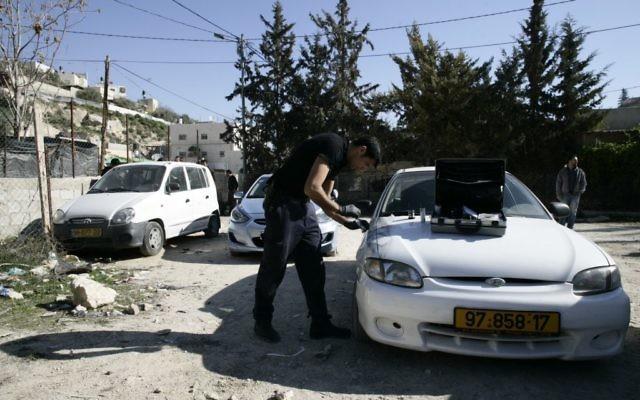 """Un policier enquête sur une voiture vandalisée par le groupe """"Prix à payer"""" dans le quartier Ein Aluza du village arabe Abu Gosh près de Jérusalem, le 10 février 2014 (Crédit : Flash90)"""