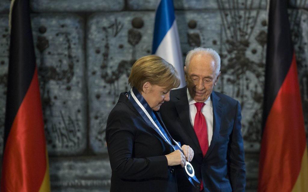 Le président Shimon Peres attribue la médaille présidentielle à la chancelière allemande Angela Merkel (Crédit : Yonatan Sindel/Flash90)