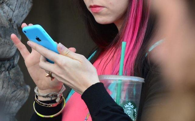 Jeune femme utilisant un smartphone de la marque Apple (Crédit : Frederic J. Brown)