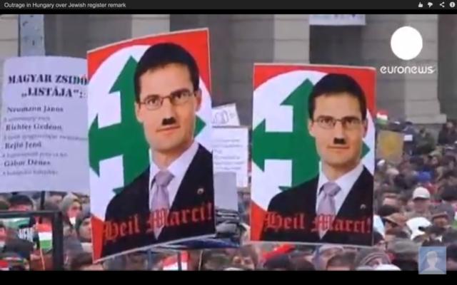 Des manifestants à Budapest brandissent des pancartes montrant le membre du parti Jobbik Marton Gyöngyosi avec la moustache d'Hitler devant l'icône du parti hongrois de la Seconde Guerre mondiale, le Parti des Croix fléchées. Un sondage récent a révélé que les juifs hongrois ont plus peur de l'antisémitisme que partout ailleurs en Europe. (Crédit : capture d'écran youtube/Euronews)
