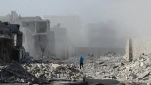 Un homme marche parmi des débris après un bombardement sur la ville d'Alep, le 31 janvier 2014  (Crédit : AFP/Mohammed Al-Khatieb)