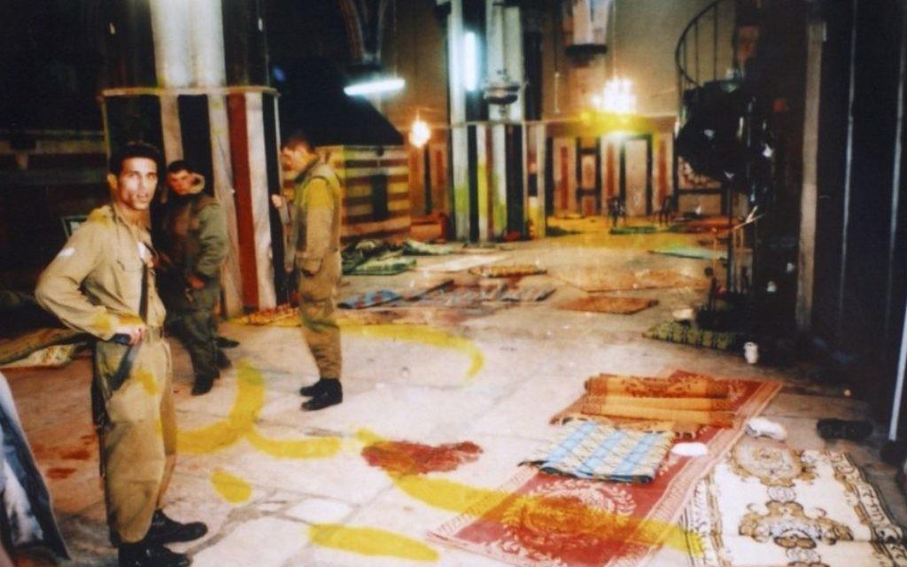 Des soldats israéliens se tiennent à côté des taches de sang au sol du hall de Yitzhak, au tombeau des Patriarches, connu en arabe sous le nom d'Al-Haram Al-Ibrahimi, suite au massacre de Goldstein, le 25 fevrier 1994 (Crédit : Flash90)