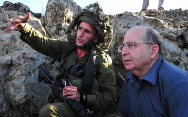 Le ministre de la Défense Moshe Yaalon (à droite) et un soldat lors d'une visite pendant un exercice de la brigade d'infanterie parachutiste sur le plateau du Golan - 2 octobre 2013 (Crédit : Ariel Hermoni/Ministère de la Défense)