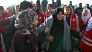 Des habitants de Homs évacués de la ville assiégée, le 9 février 2014, en Syrie. (Crédit : Sana/AFP)