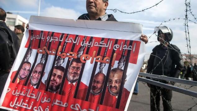 Un manifestant brandit une banderole montrant le président destitué Mohamed Morsi avec ses co-accusés, devant le siège de la police du Caire, le 1er février 2014 (Crédit : AFP/Archives Mahmoud Khaled)