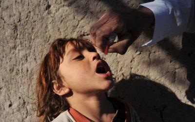 Une petite afghane reçoit un vaccin contre la polio d'un médecin lors d'une campagne de vaccination des enfants contre la polio dans la province de Nangarhar, 25 février 2014 (Crédit : AFP Photo/Noorullah Shirzada)