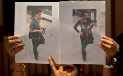Un journaliste pointe du doigt la photographie du passager iranien Pouria Noor Mohammad Mehrdad (à gauche) alors qu'un policier malaisien montre les photographies des deux hommes ayant embarqué à bord du vol MH 370 avec des passeports européens volés, à Sepang (près de l'aéroport international de Kuala Lumpur), le 11 mars 2014 (Crédit : AFP PHOTO / MANAN VATSYAYANA)