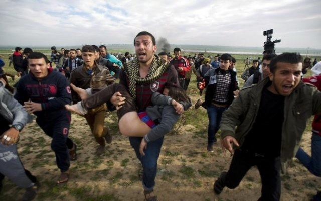 Des Gazaouis portent un jeune garçon blessé par les forces armées israéliennes à la frontière (Crédit : Mahmud Hams/AFP)
