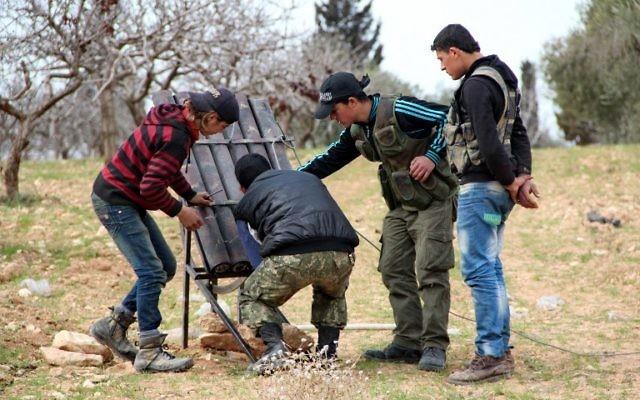 Des combattants en Syrie lancent des roquettes vers les forces gouvernementales à Khan Sheikhun (Crédit : AFP Photo/Al-Maarra Today/Ghaith Omran)