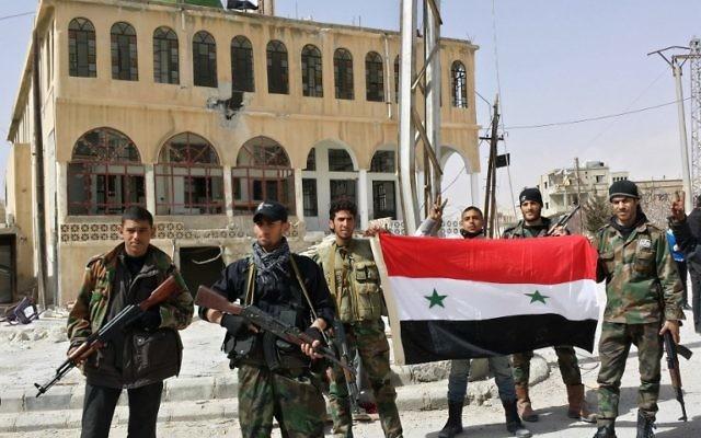 Des soldats pro-gouvernement affichent le drapeau syrien et posent pour une photo dans le village d'al-Sahel, près de Yabroud (Crédit : AFP/STR)