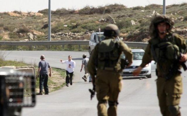 Des soldats israéliens près d'habitants des implantations qui auraient attaqué vendredi la voiture d'un photographe, à côté de l'implantation de Beit El en Cisjordanie (Crédit : AFP)