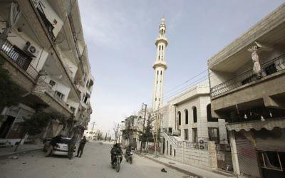 Des membres des forces pro-gouvernementales circulent dans les rues désertes de Yabroud après que les forces du régime, aidées du Hezbollah, aient repris le contrôle de la ville, le 16 mars 2014 (Crédit : AFP/JOSEPH EID)