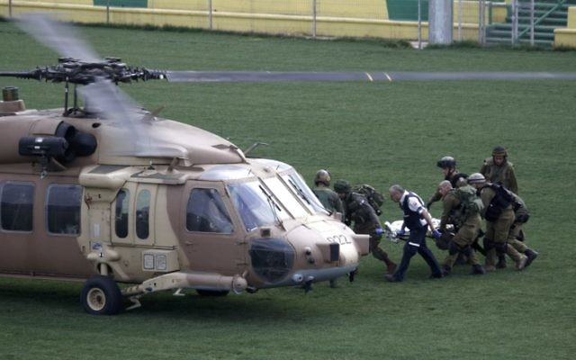 Des soldats israéliens transportent un soldat, blessé lors d'une explosion au plateau du Golan, vers un hélicoptère, le 18 mars 2014 (Crédit : AFP/Jalaa Marey)