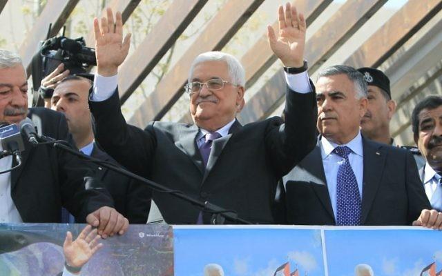 Le président de l'Autorité palestinienne Mahmoud Abbas salue les foules à son retour de sa visite officielle aux Etats-Unis, le 20 mars 2014 (Crédit : Abbas Nomani/AFP Photo)