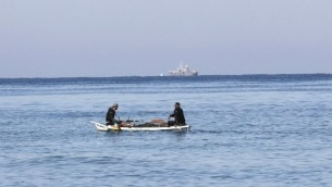 Des pêcheurs palestiniens assis dans leur barque à proximité du rivage de Rafah, au sud de Gaza ; un bateau de police israélien apparaît au loin, le 26 mars 2014. (Crédit : AFP/Said Khatib)