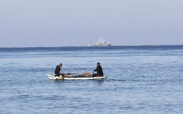 Des pêcheurs palestiniens assis dans leur barque à proximité du rivage de Rafah, au sud de Gaza ; un bateau de police israélien apparaît au loin, le 26 mars 2014. (Crédit : Said Khatib/AFP)