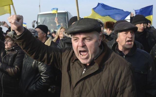 Des Ukrainiens manifestent au poste de contrôle qui bloque l'entrée en Crimée, le 7 mars 2014 (Crédit : Alexander Nemenov/AFP)