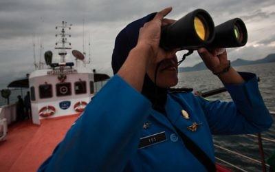 Un membre de l'équipe de secours nationale malaisienne scrute l'horizon sur la mer d'Andaman à la recherche du vol MH 370 (Crédit : AFP/CHAIDEER MAHYUDDIN)